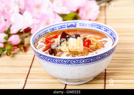 Chinese hot and sour soup served in a bowl. - Stock Photo