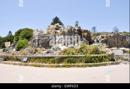 Rugged limestone rock bluffs with plants under a clear blue sky along the foreshoe of Cottesloe Beach in Western - Stock Photo