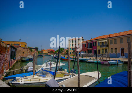 MURANO, ITALY - JUNE 16, 2015: Various boats parking on Murano canals outside of people houses, nice view in sunny - Stock Photo