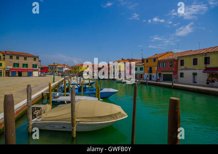 MURANO, ITALY - JUNE 16, 2015: Wooden port at Murano city, parking boats in canal and colored houses on the sides - Stock Photo