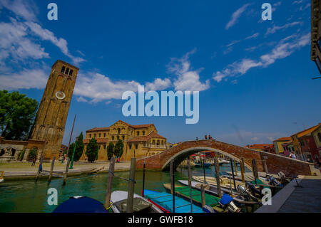 MURANO, ITALY - JUNE 16, 2015: Murano's Cathedral and tower view from the other side of the canal, boats parking - Stock Photo