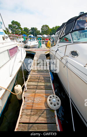 A view of the jetty with private motor yachts, docked in the marina. - Stock Photo