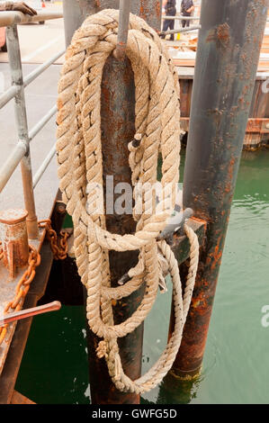 Coiled mooring rope at the marine pier. - Stock Photo