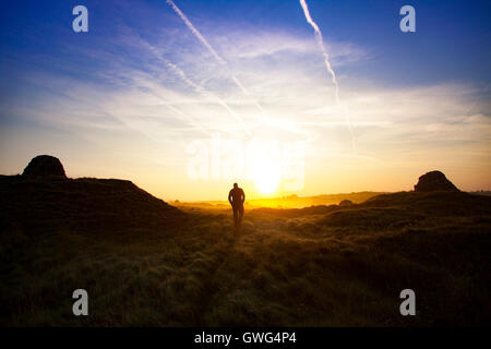 A walker enjoying the sunrise overlooked either side by old lead mine shafts as the morning mist and fog covers - Stock Photo