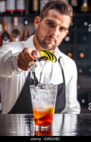 Barman decorating cocktail with lime - Stock Photo