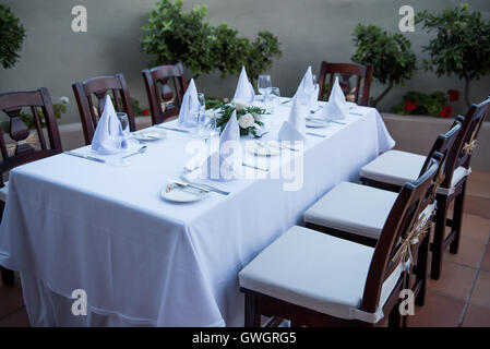 Festively laid table with white tablecloths  glasses and plates - Stock Photo