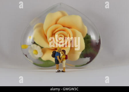 Selective focus on miniature of young couple romantic kiss in front of a yellow flower background. - Stock Photo