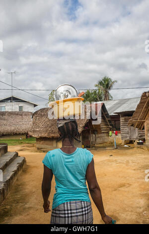 Maroon woman carrying bowl with dishes on her head in Suriname - Stock Photo