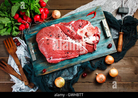 Fresh beef veal meat on rustic wooden table with kitchen utensils and vegetables, top view - Stock Photo