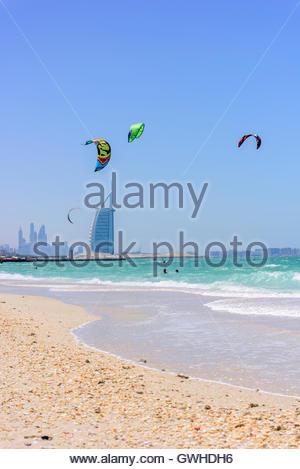 man kite-surfing at Jumeirah Kite Beach with Burj Al Arab in background. Dubai, United Arab Emirates. - Stock Photo