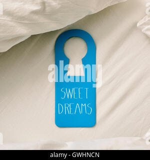 closeup of a blue door hanger with the text sweet dreams written in it, placed on a comfortable bed - Stock Photo