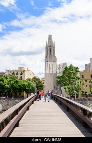 People crossing the pedestrian only Pont de Sant Feliu overlooked by the Basílica de Sant Feliu, Girona, Catalonia, - Stock Photo