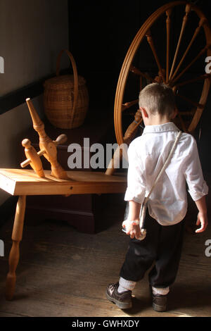 Little boy observing a spinning wheel at Frontier Culture Museum in Staunton, Virginia - Stock Photo