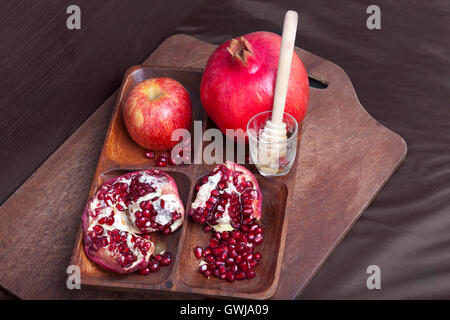 Pomegranates and apple with honey on wooden board - Stock Photo