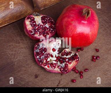 Ripe open pomegranate on wooden background - Stock Photo