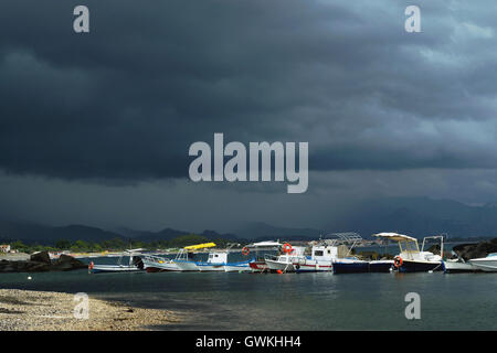 Small traditional fishing boats in the pier, dramatic sky over, copy space - Stock Photo