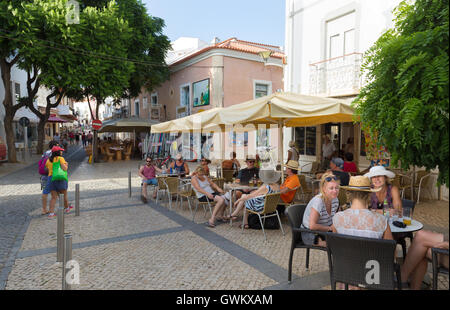 People sitting drinking at a street cafe, Lagos, Algarve, Portugal, Europe - Stock Photo