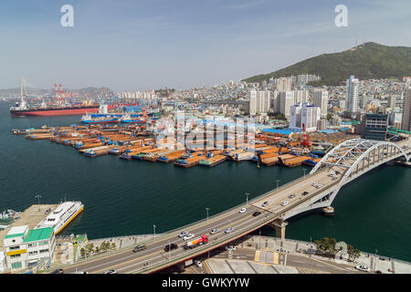 View of the city and barges and cargo ships at a busy port above in Busan, South Korea. - Stock Photo