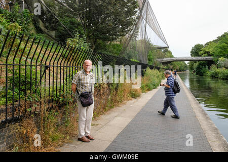 Tourists on the Regent's Canal towpath near Bridge 11 and the Snowdon Aviary of London Zoo - Stock Photo