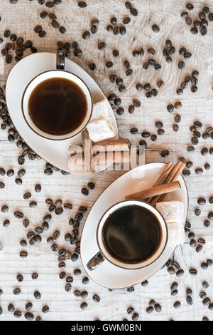 Cup of coffee with grains, croissant, turkish delight and cinnamon sticks on wooden background - Stock Photo