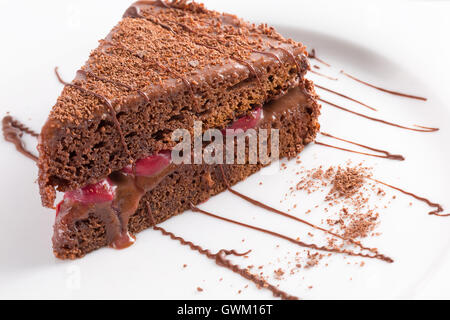 chocolate cheese cake with cherries on white plate. - Stock Photo