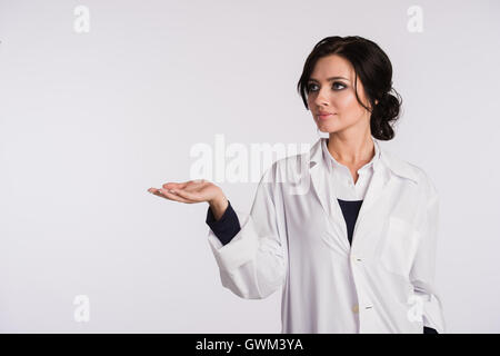 Pointing to blank copy space woman doctor nurse over white background - Stock Photo