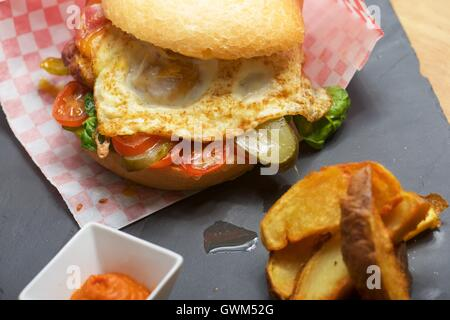 Beef burger with fried egg and chips. - Stock Photo