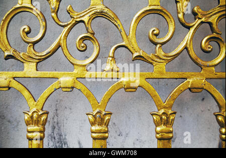 Gold old wrought fence close-up background. Forged ornate beautiful pattern golden  gate at shrine - Stock Photo
