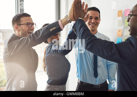 Happy successful multiracial business team giving a high fives gesture as they laugh and cheer their success - Stock Photo