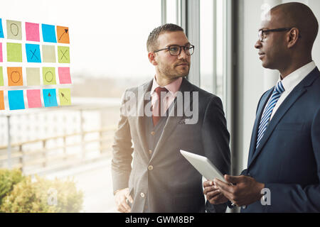 Caucasian and African businessman in a meeting standing in front of colorful memos on the glass of a window in the - Stock Photo