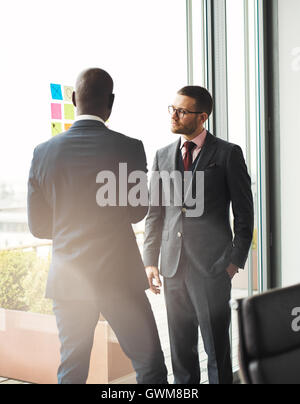 Serious young businessman wearing glasses standing in front of a bright window overlooking a patio talking to an - Stock Photo