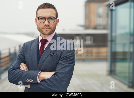 Confident stylish businessman wearing glasses standing on an open-air balcony looking thoughtfully at the camera - Stock Photo