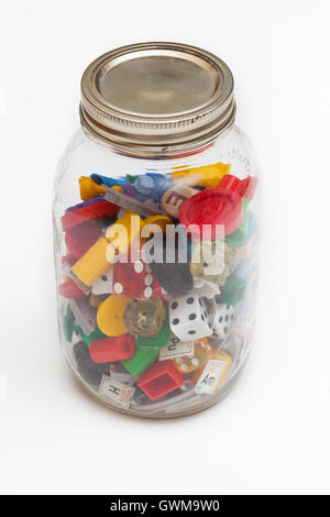 An old jar filled with a variety of old game pieces - Stock Photo