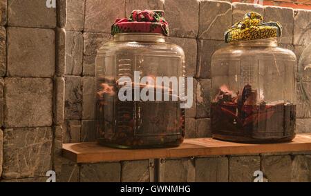 Jars of ya dong (Thai white spirits with medicinal herbs) at a bar in Bangkok, Thailand - Stock Photo