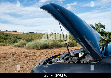 Close up of a broken down car, engine open, in a rural area - Stock Photo