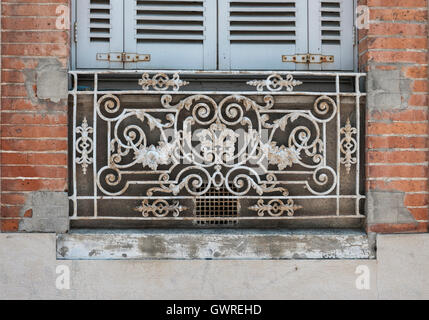 Window with blue shutters and ornate wrought iron window box or balcony on old brick building in Toulouse, France. - Stock Photo