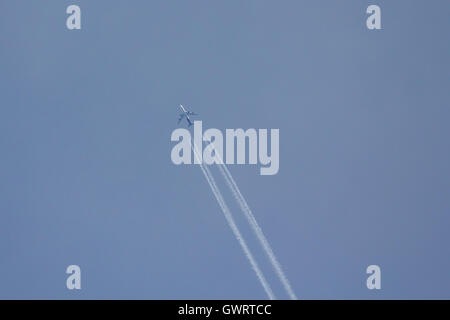 Airplane in the blue sky with condensation trail - Stock Photo
