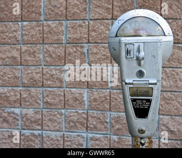 retro parking meter on brick wall background - Stock Photo