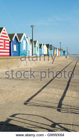 Brightly coloured beach huts on the sea front with the shadow of safety railings  cast along North Parade, Southwold, - Stock Photo
