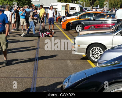 Amsterdam, The Netherlands - September 10, 2016: Man lying on ground photographing cars on display during Cars & - Stock Photo