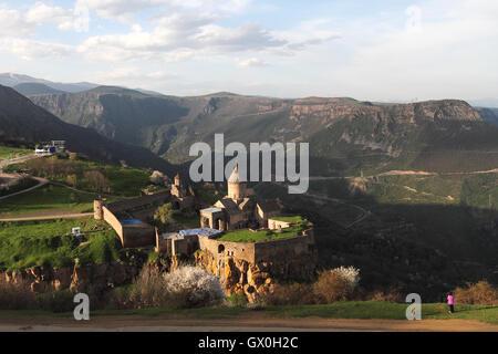 Woman in purple photographing the Tatev Monastery in Armenia. - Stock Photo