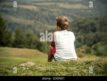 Boy sitting on a hill and looks into the distance. Childhood, dreams, freedom - a concept. - Stock Photo