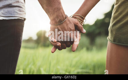 Young couple walking through meadow hand in hand. Close up shot with focus on hands of man and woman. - Stock Photo