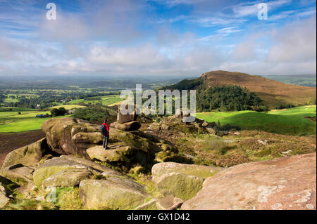 A walker stood on Ramshaw Rocks looking towards Hen Cloud at the Roaches, Peak District National Park, Staffordshire. - Stock Photo