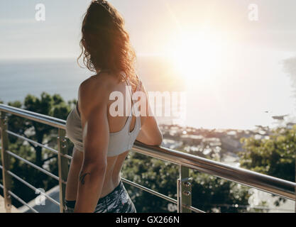 Rear view shot of woman standing by a railing in balcony and looking away on a bright sunny day. - Stock Photo