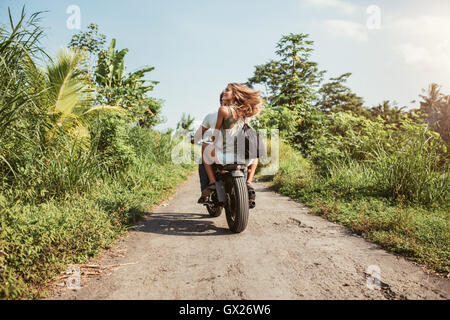 Rear view of young couple riding motorcycle on rural road. Woman with her boyfriend riding on motorbike on a summer - Stock Photo