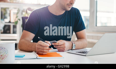 Cropped shot of young businessman sitting in office and working at his desk. Close up of male office worker with - Stock Photo