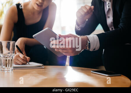 Business colleagues working together in office, focus on man using electronic organizer in foreground and woman - Stock Photo