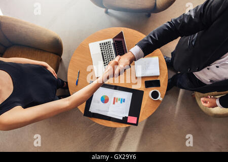 Top view of young business partners shaking hands over deal at office. Focus on handshake. - Stock Photo