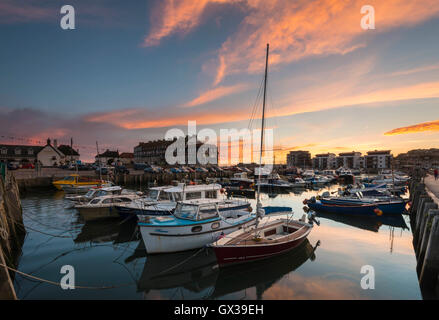 West Bay, Dorset, UK - 14th September 2016. UK Weather.  A glorious sunset illuminating the clouds above West Bay Harbour in Dorset, UK.  West Bay is one of the locations for the hit ITV series Broadchurch.  Picture: Graham Hunt/Alamy Live News